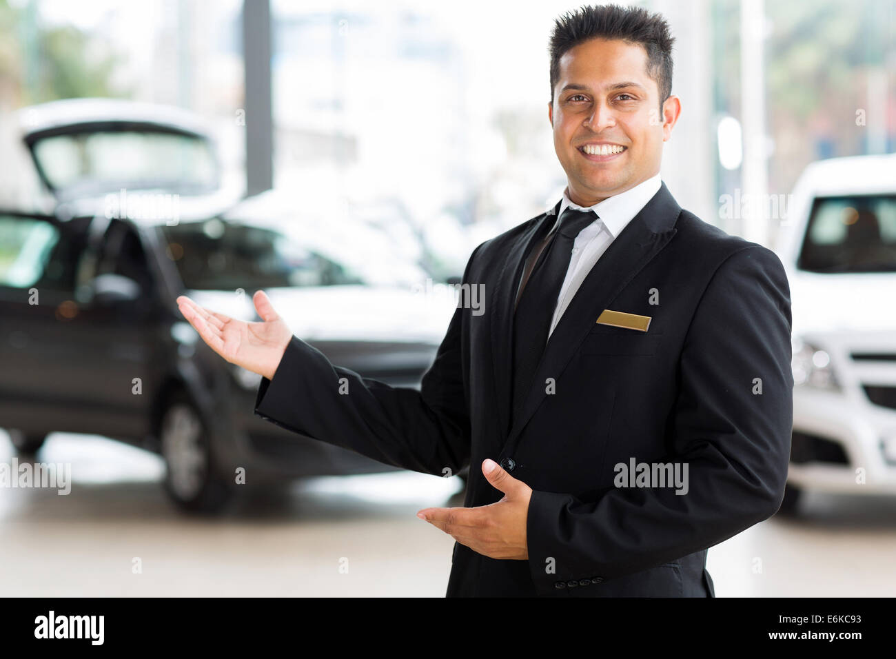 handsome Indian salesman presenting new car to clients - Stock Image
