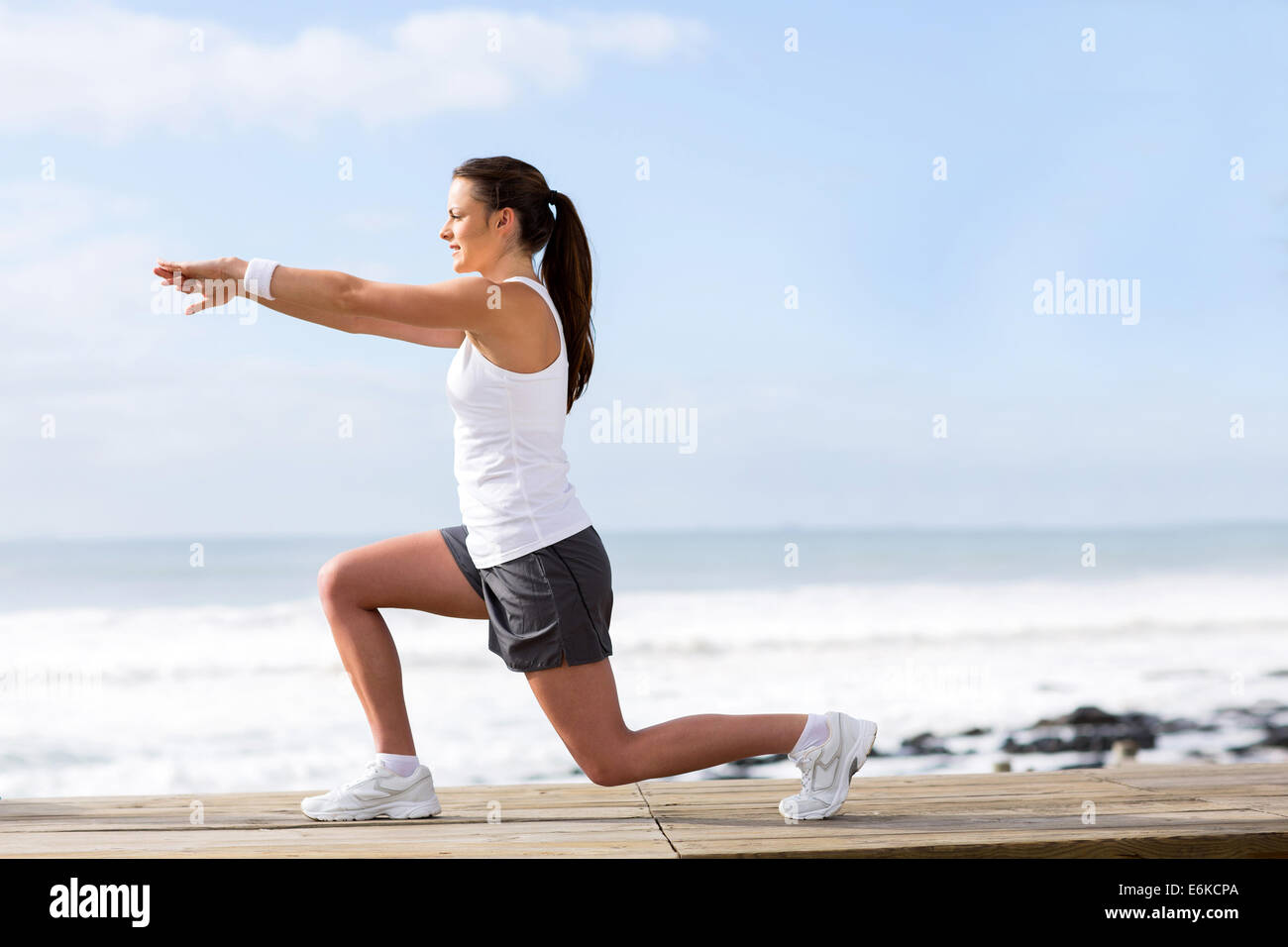 healthy woman working out outdoors at beach - Stock Image