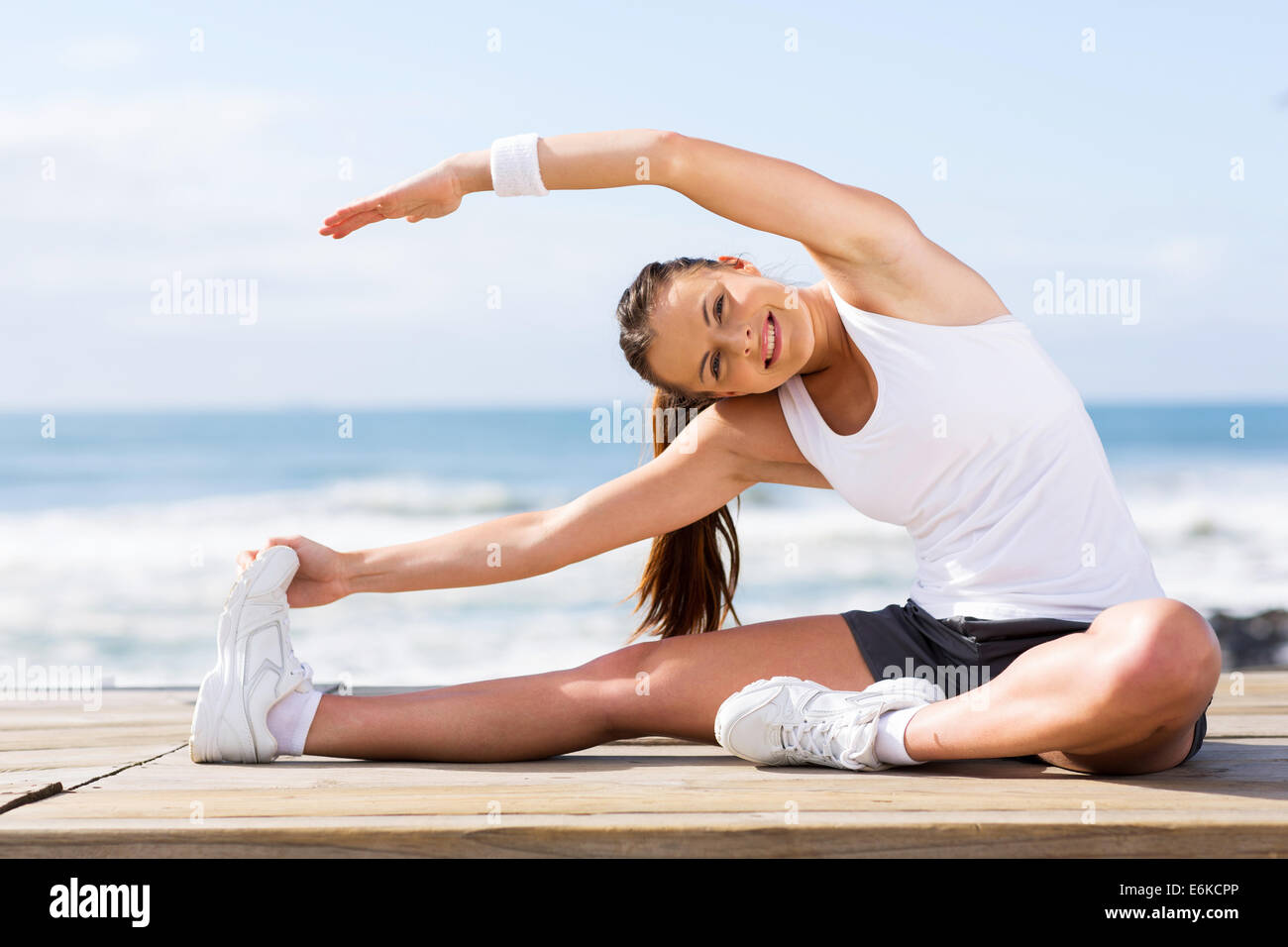 beautiful young girl working out at the beach - Stock Image