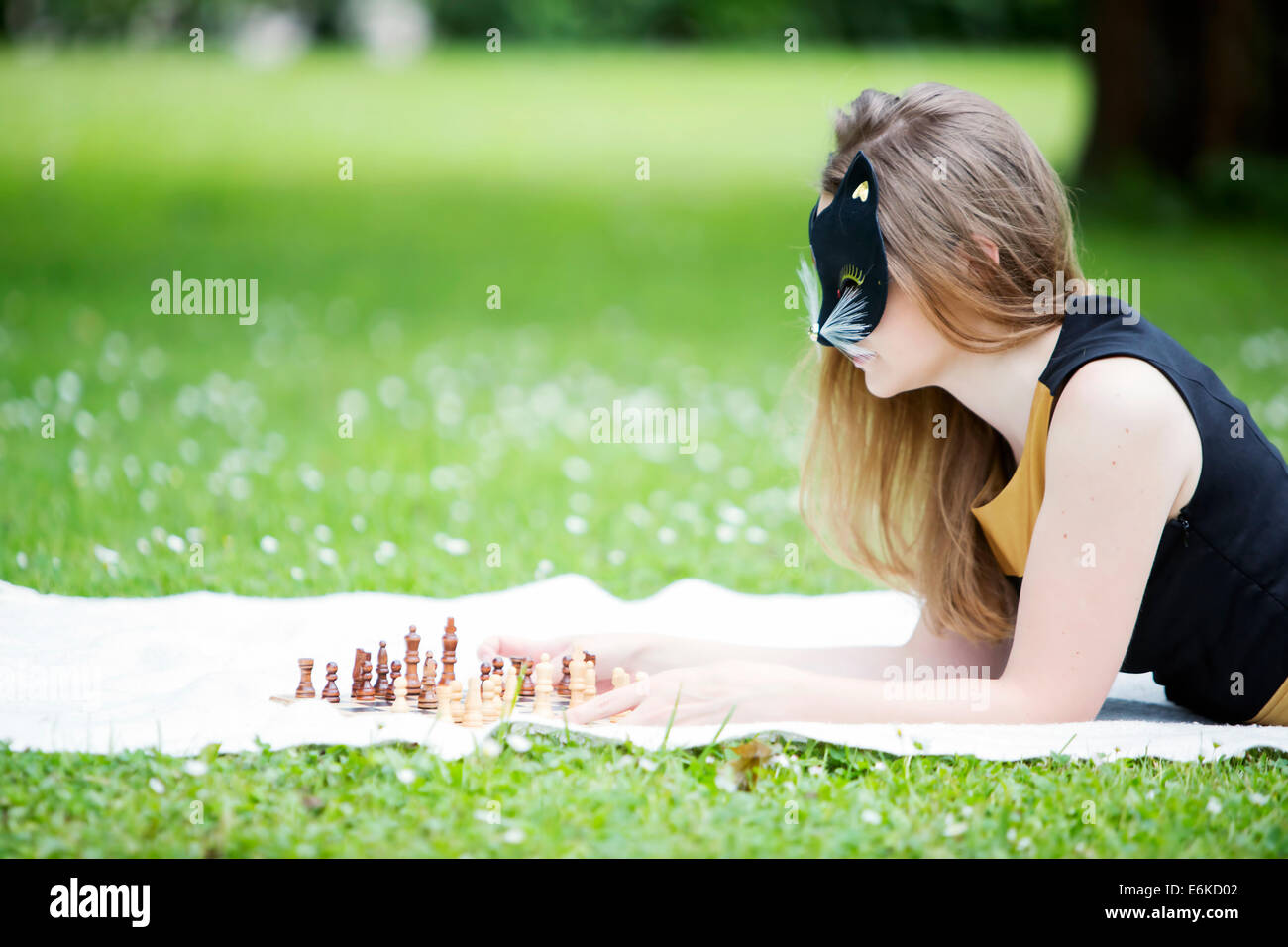 Young woman  with mask decide move chess piece - Stock Image