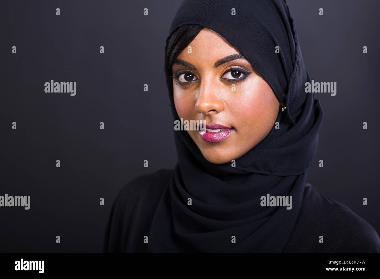 pretty young Muslim woman head shot over black background Stock Photo