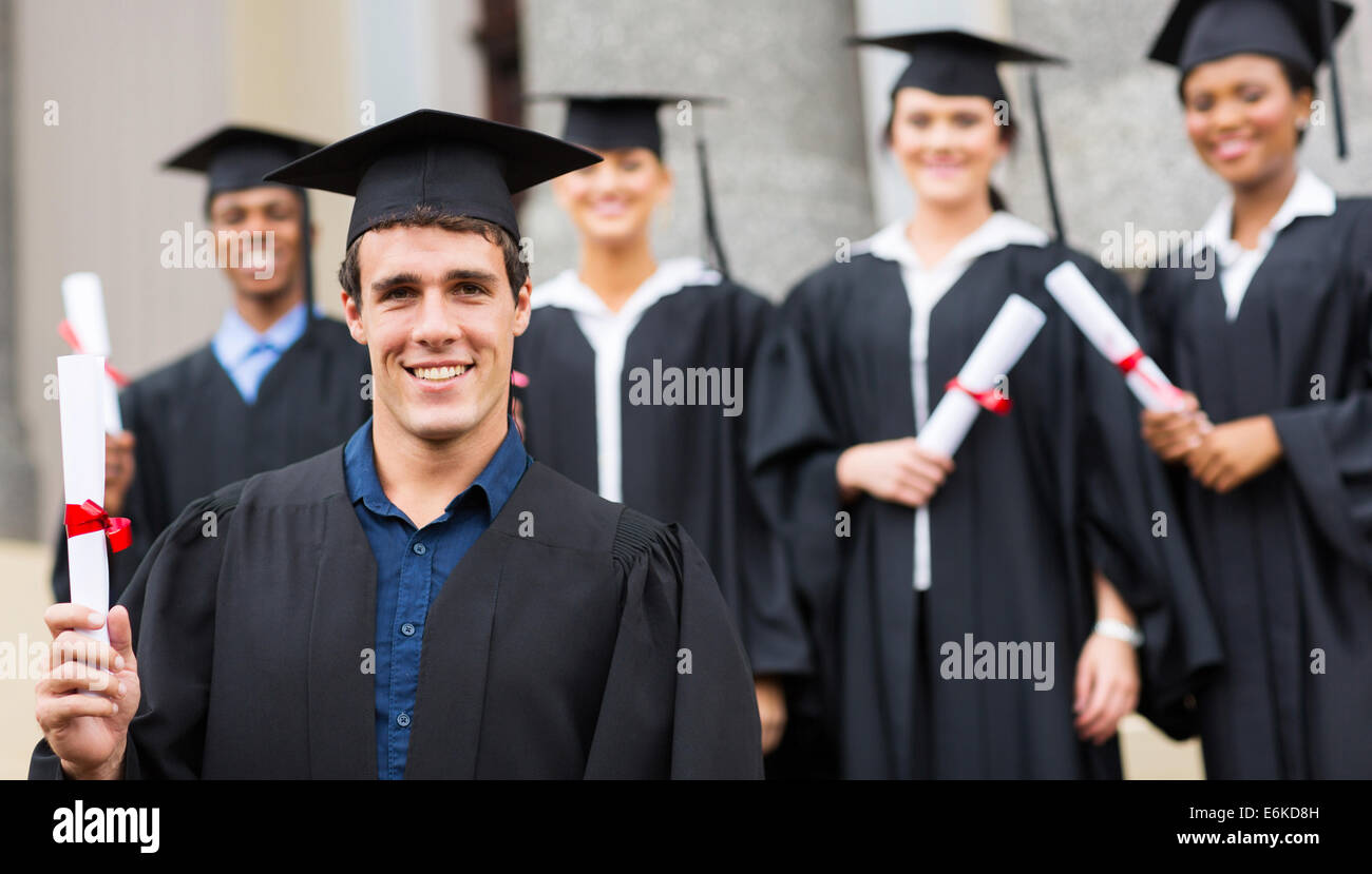 handsome male university graduate holding his diploma - Stock Image