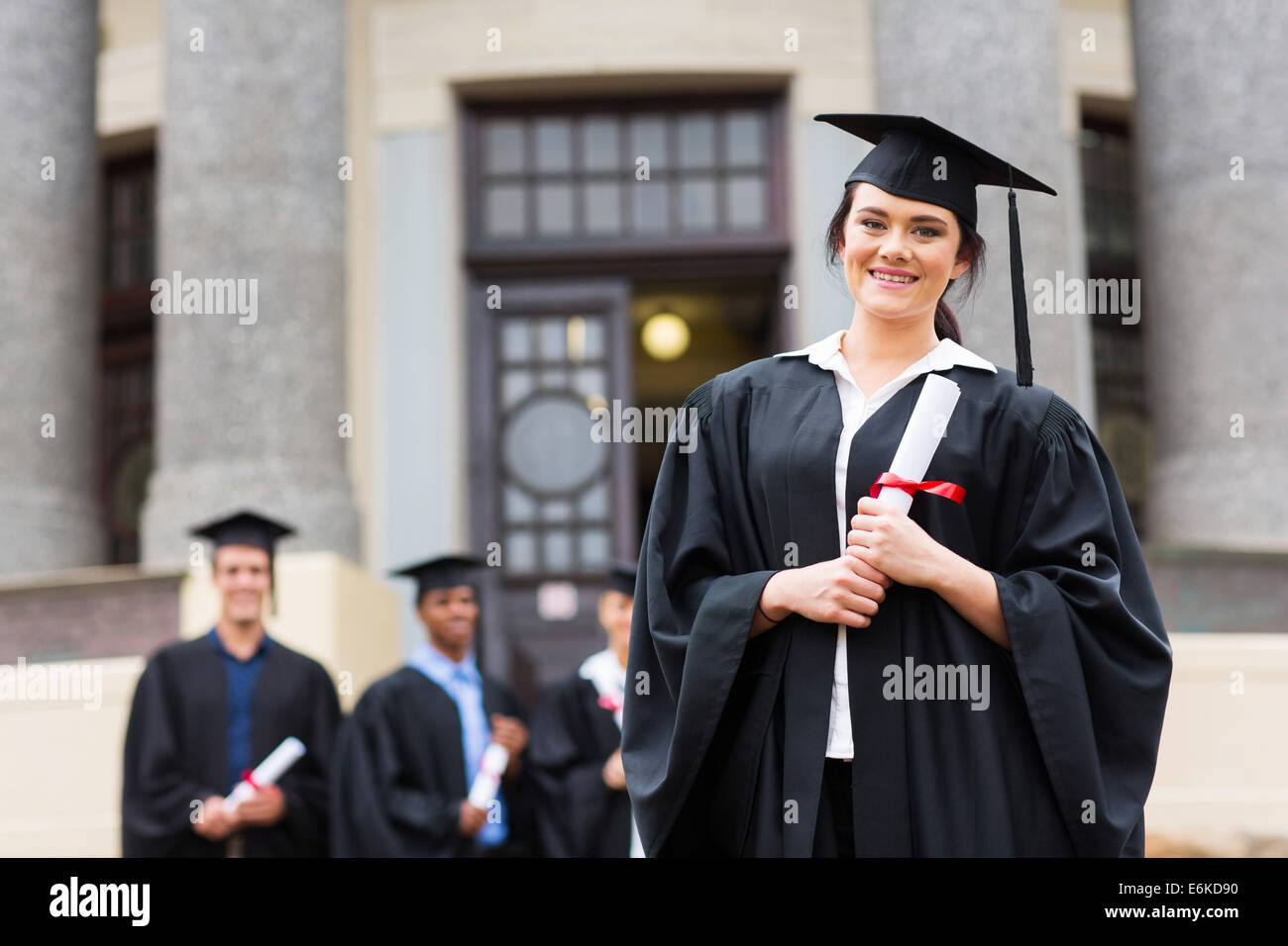 portrait of pretty female graduate wearing graduation gown at ...