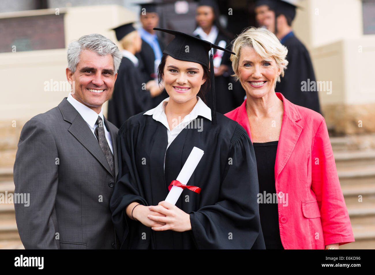 pretty young graduate with happy parents at graduation ceremony - Stock Image