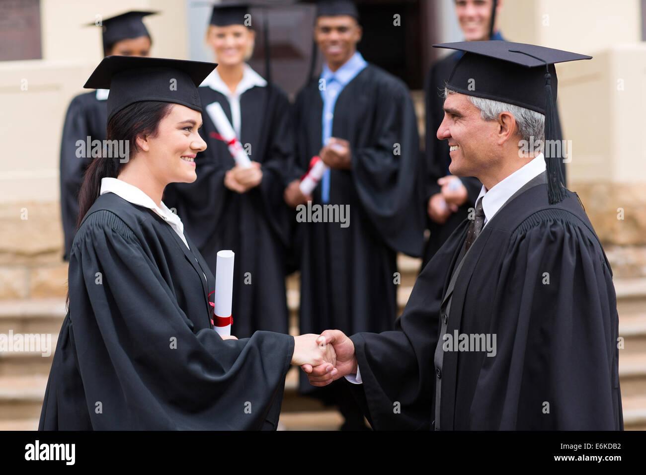 beautiful female graduate handshaking with dean - Stock Image