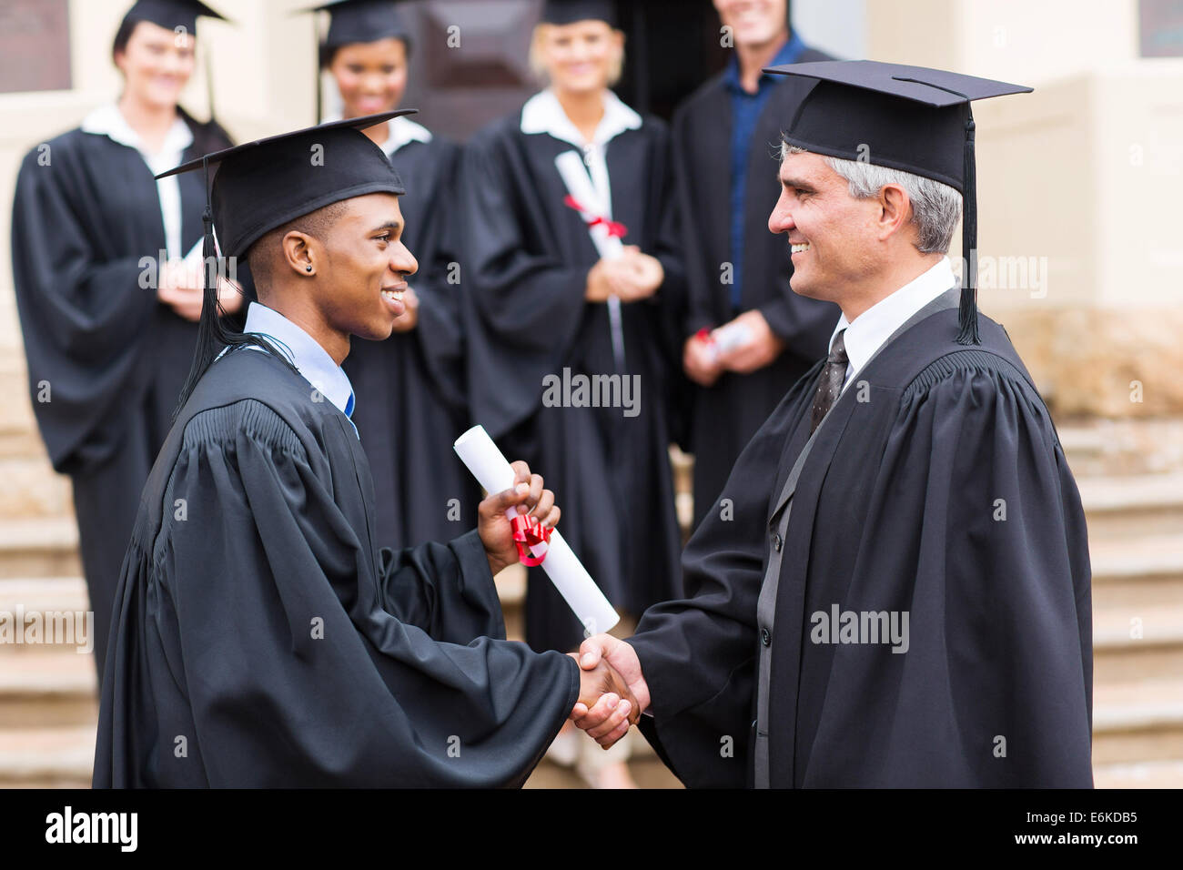happy African male graduate handshaking with dean - Stock Image