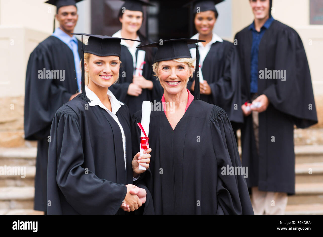 pretty female graduate handshaking with dean - Stock Image