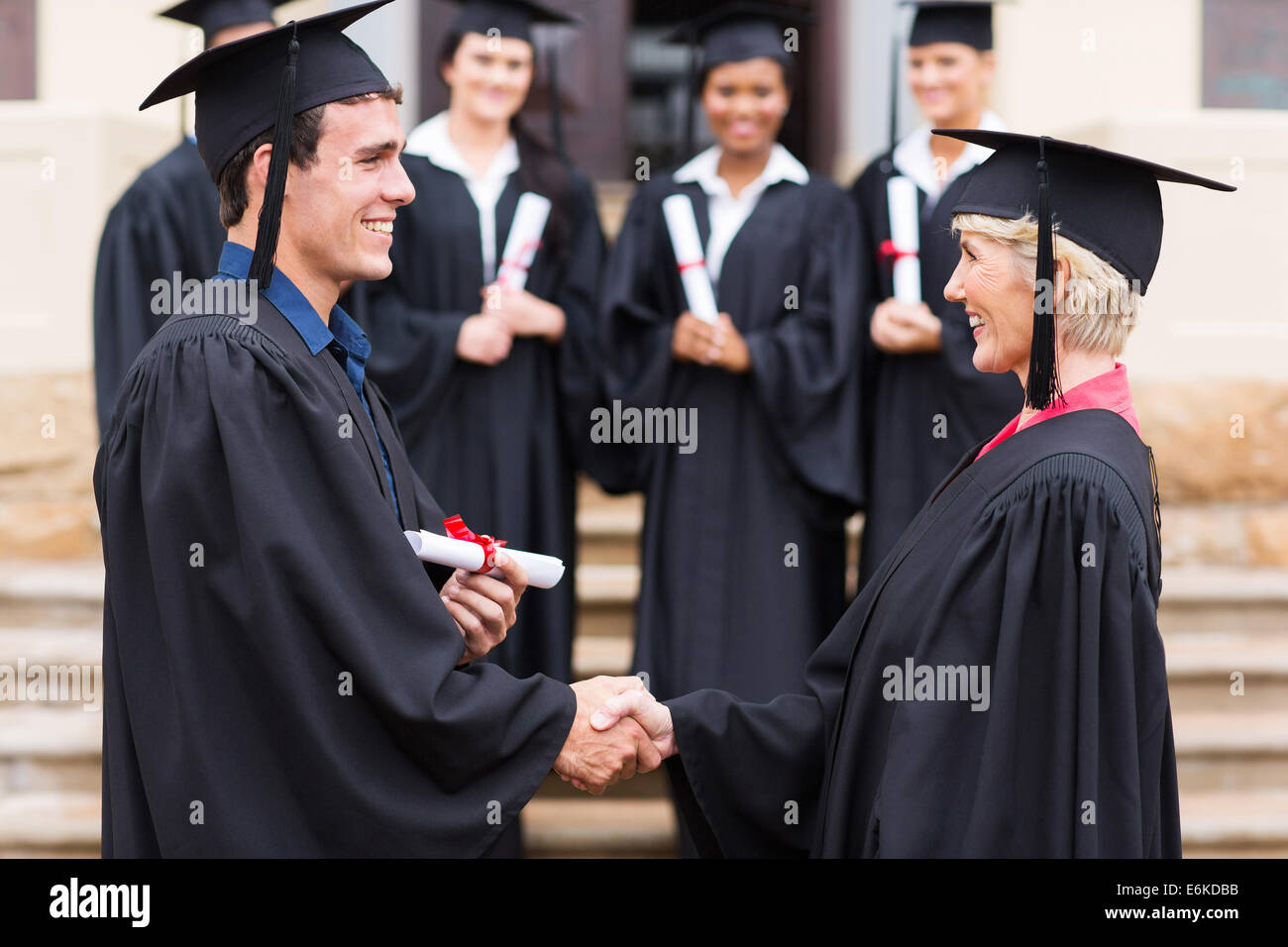 happy young graduate shaking hand with professor - Stock Image