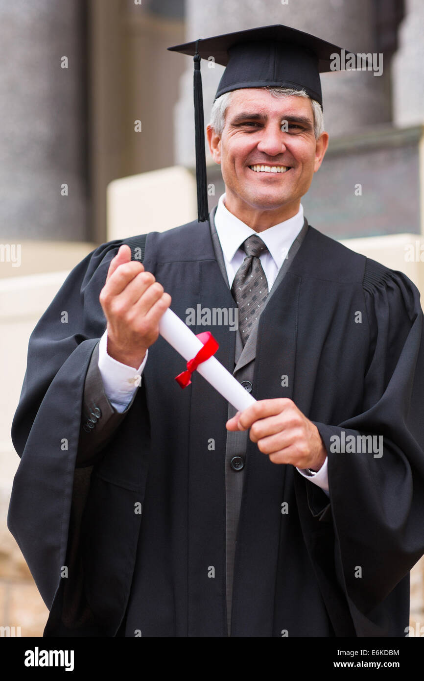 smiling middle aged male graduate in front university building - Stock Image