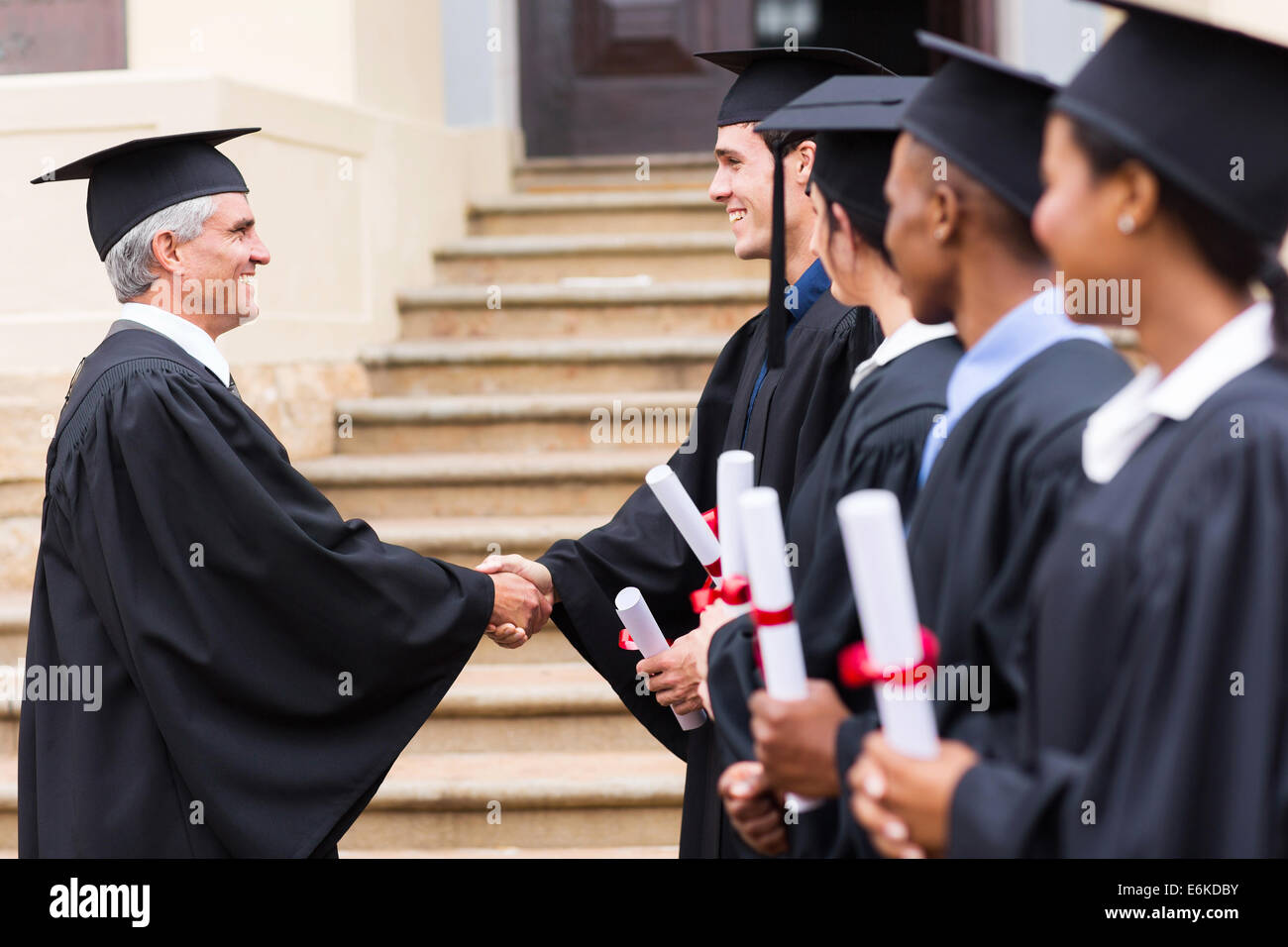 group of cheerful graduates in line handshaking with dean - Stock Image