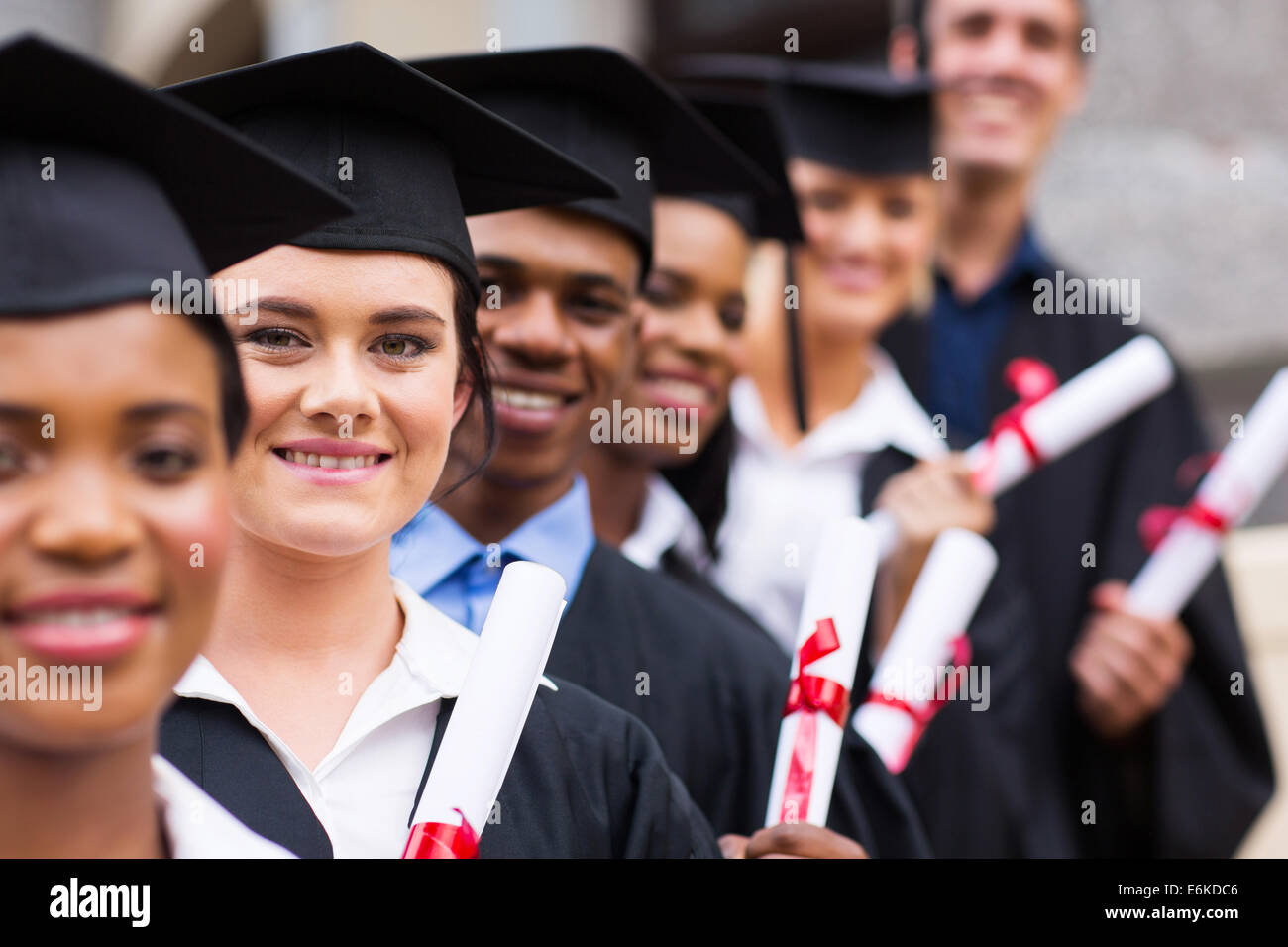 group of happy college graduates standing in a row - Stock Image