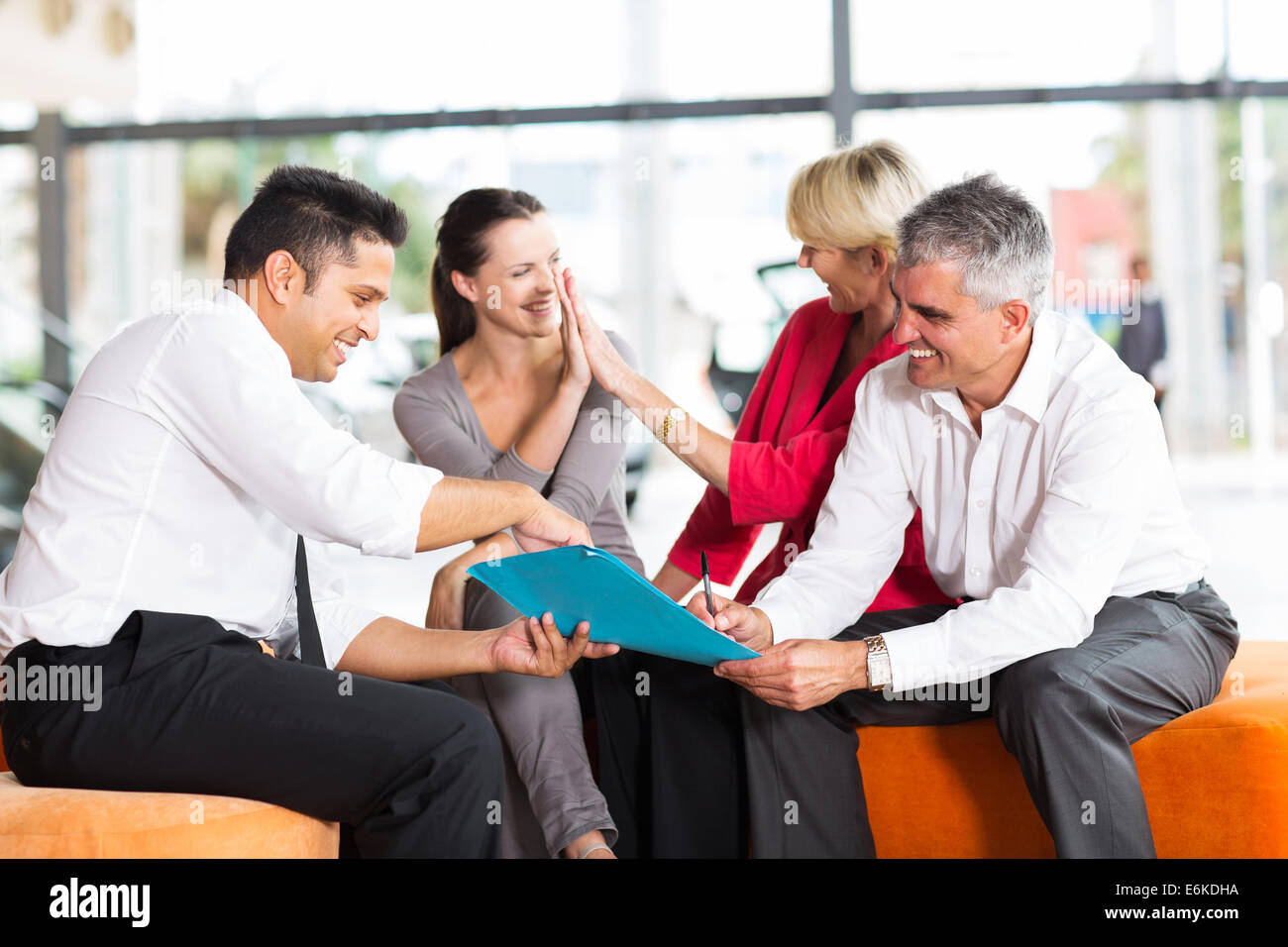 happy family buying a new car at vehicle showroom - Stock Image