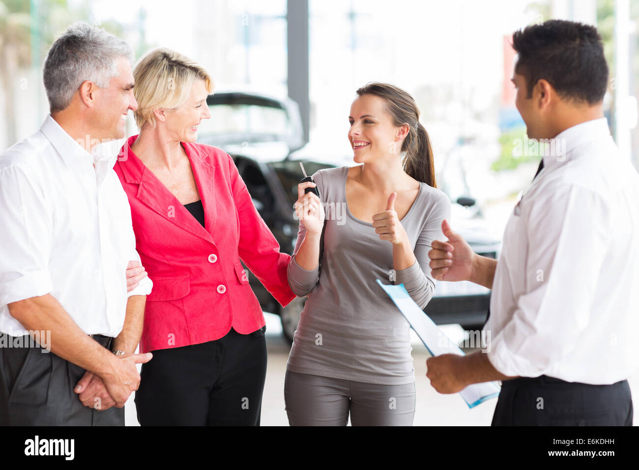 happy young adult daughter receiving a new car from her parents - Stock Image