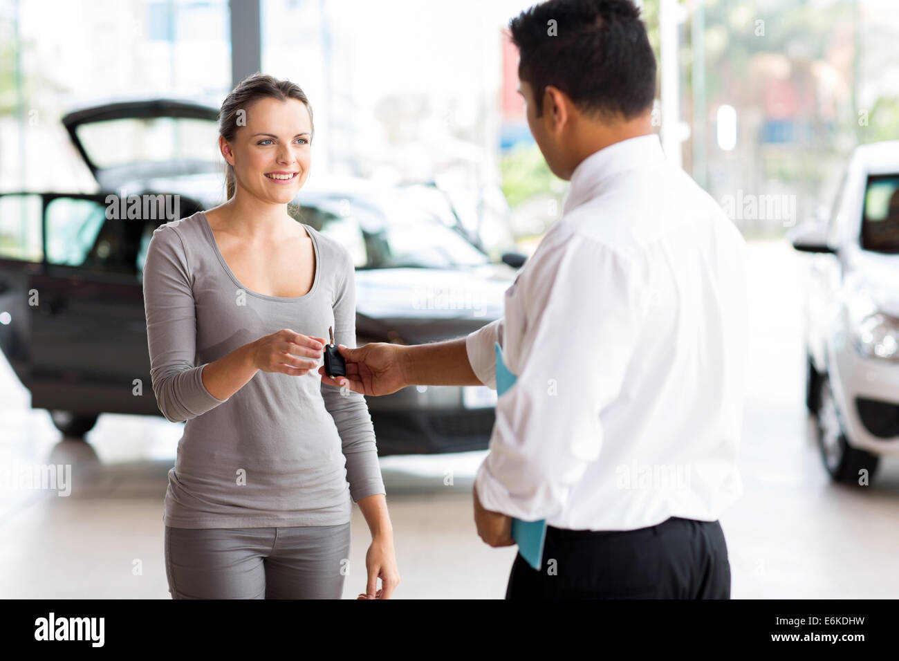 young woman receiving her new car key from salesman - Stock Image