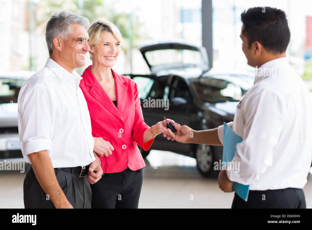 senior couple receiving car key after buying a new car - Stock Image
