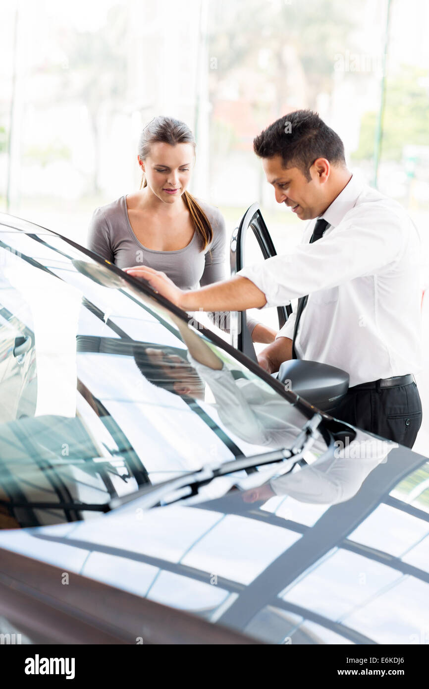 car sales consultant showing a new car to a potential buyer in showroom - Stock Image