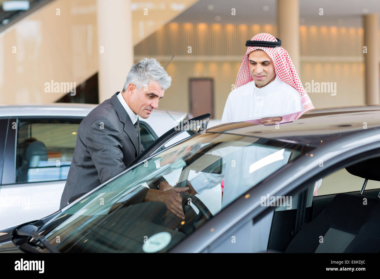middle aged car dealer showing new car to potential Arabian buyer - Stock Image
