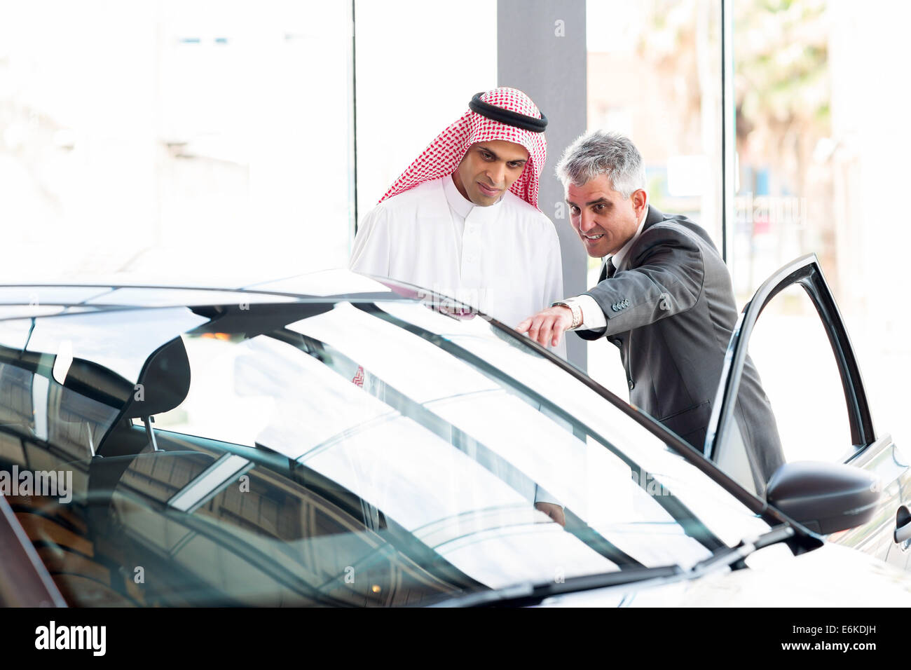 senior dealer pointing car features to potential Arabian buyer - Stock Image