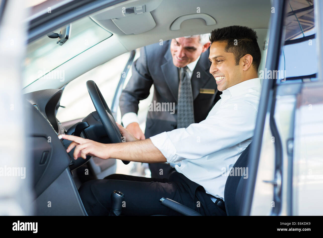 happy Indian man checking car features at showroom - Stock Image