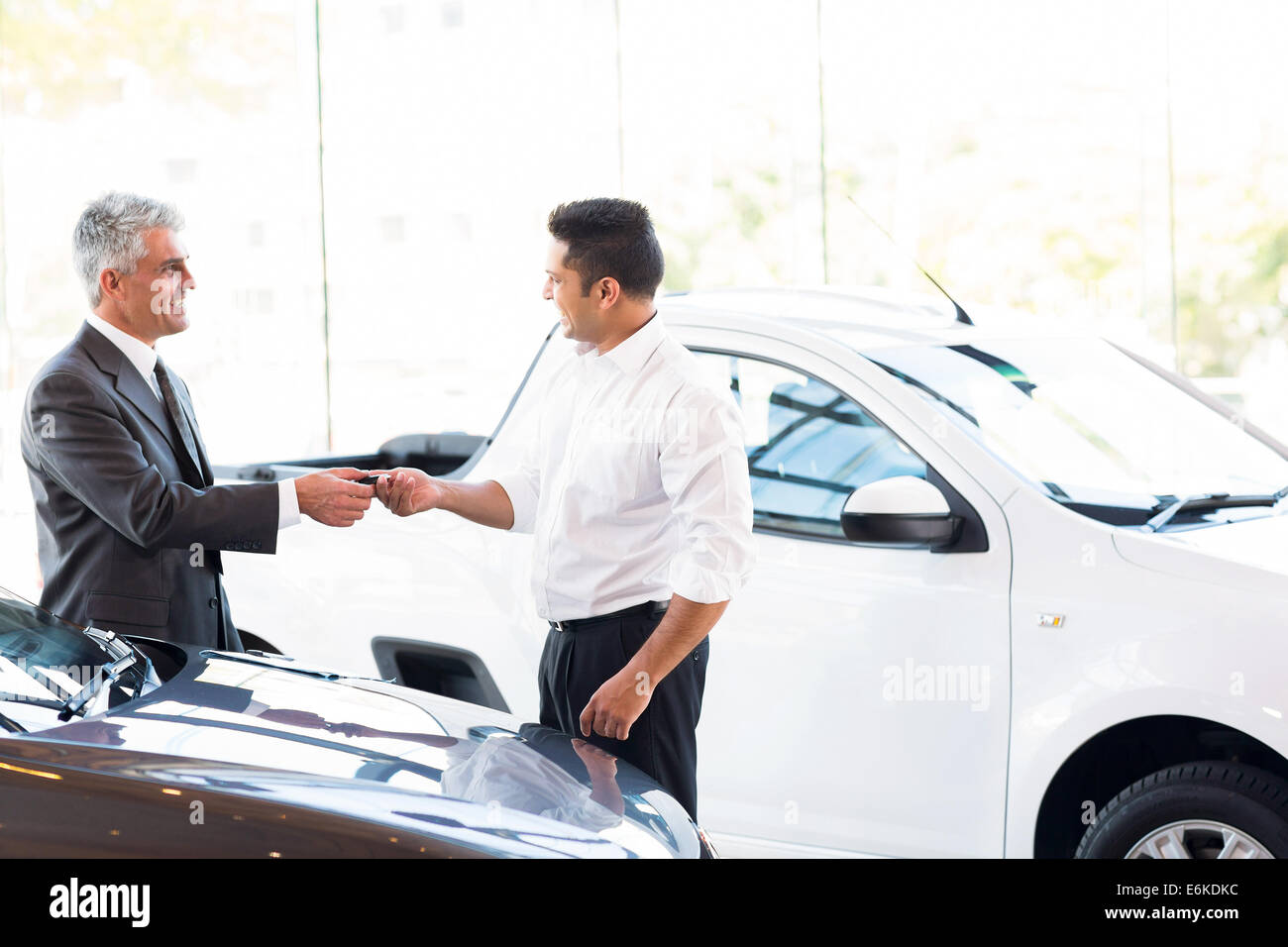 senior car salesman handing over new car key to customer at showroom - Stock Image