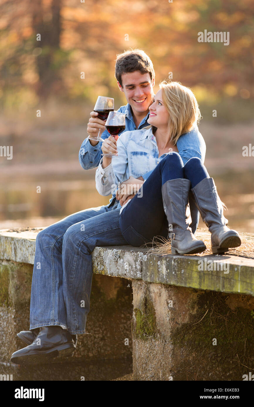 romantic couple drinking red wine outdoors - Stock Image