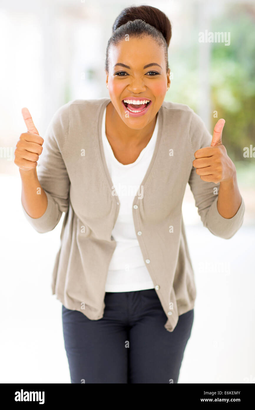 cheerful African woman giving two thumbs up as sign of approval - Stock Image