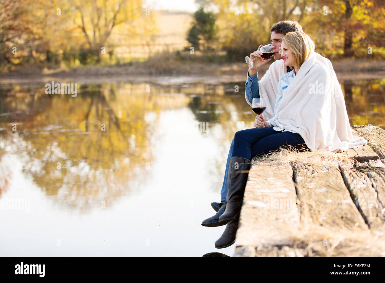 happy couple enjoying spend time together by the autumn lake together - Stock Image