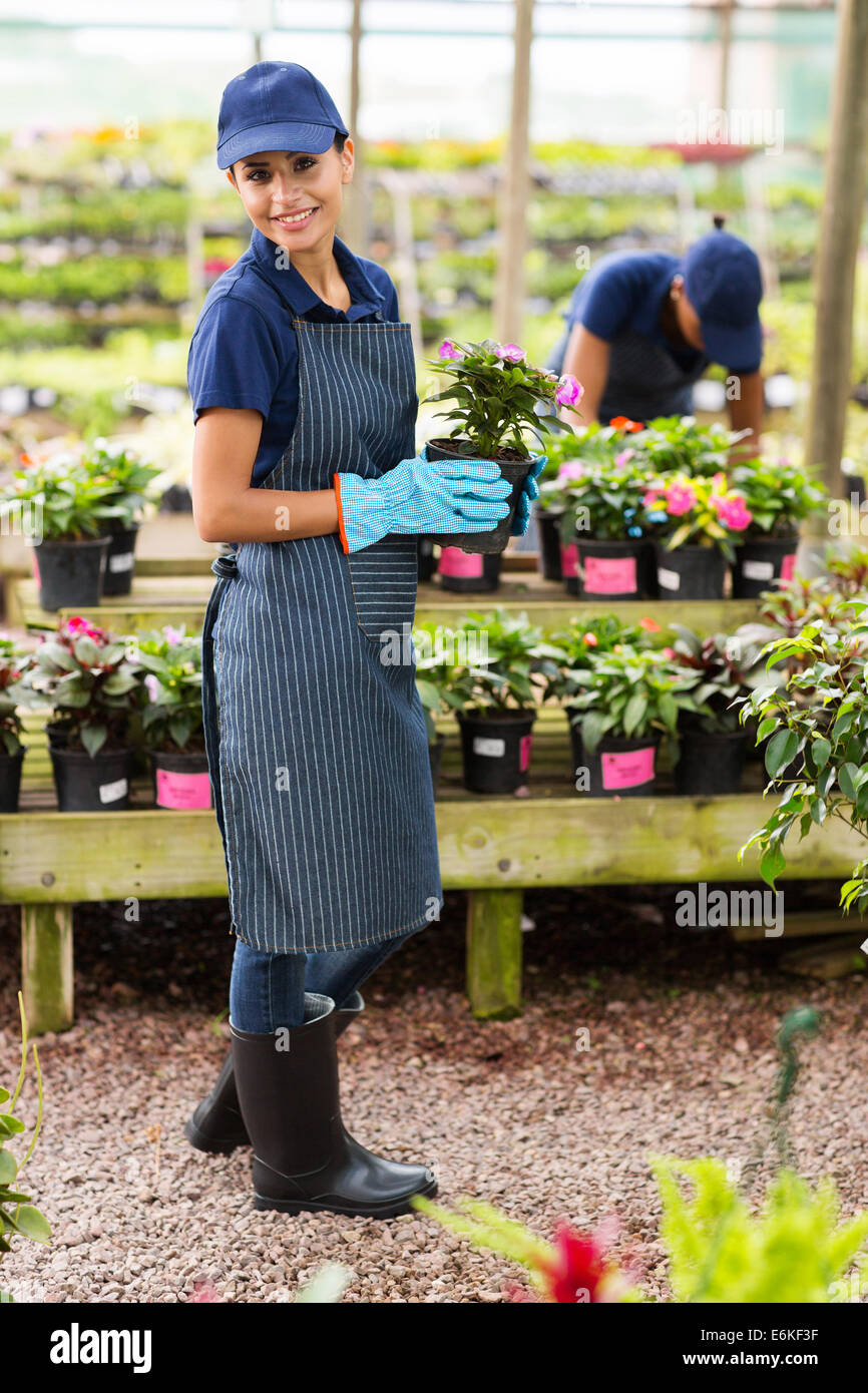 portrait of young florist holding a pot of flowers in greenhouse - Stock Image