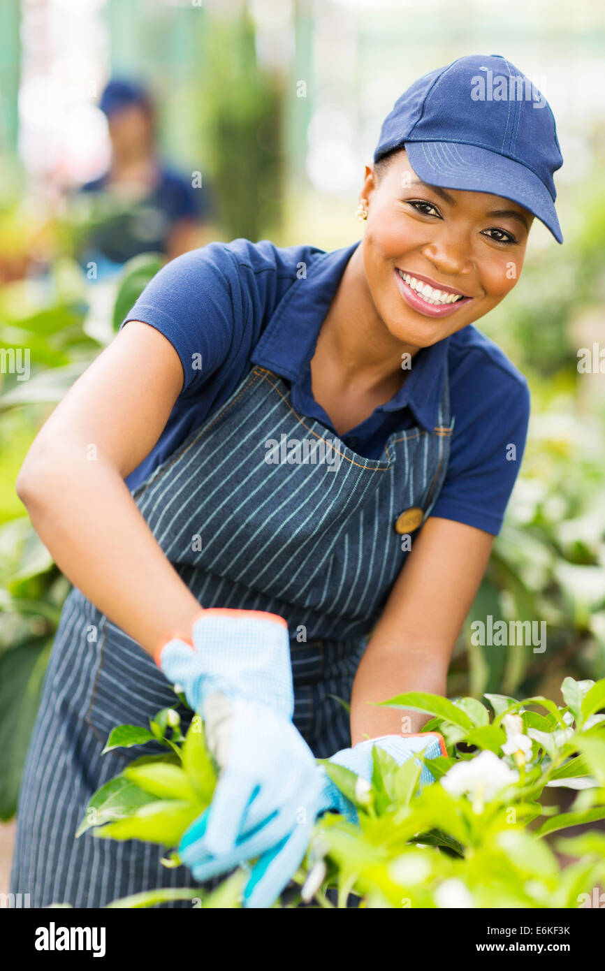 happy young African American nursery worker gardening - Stock Image
