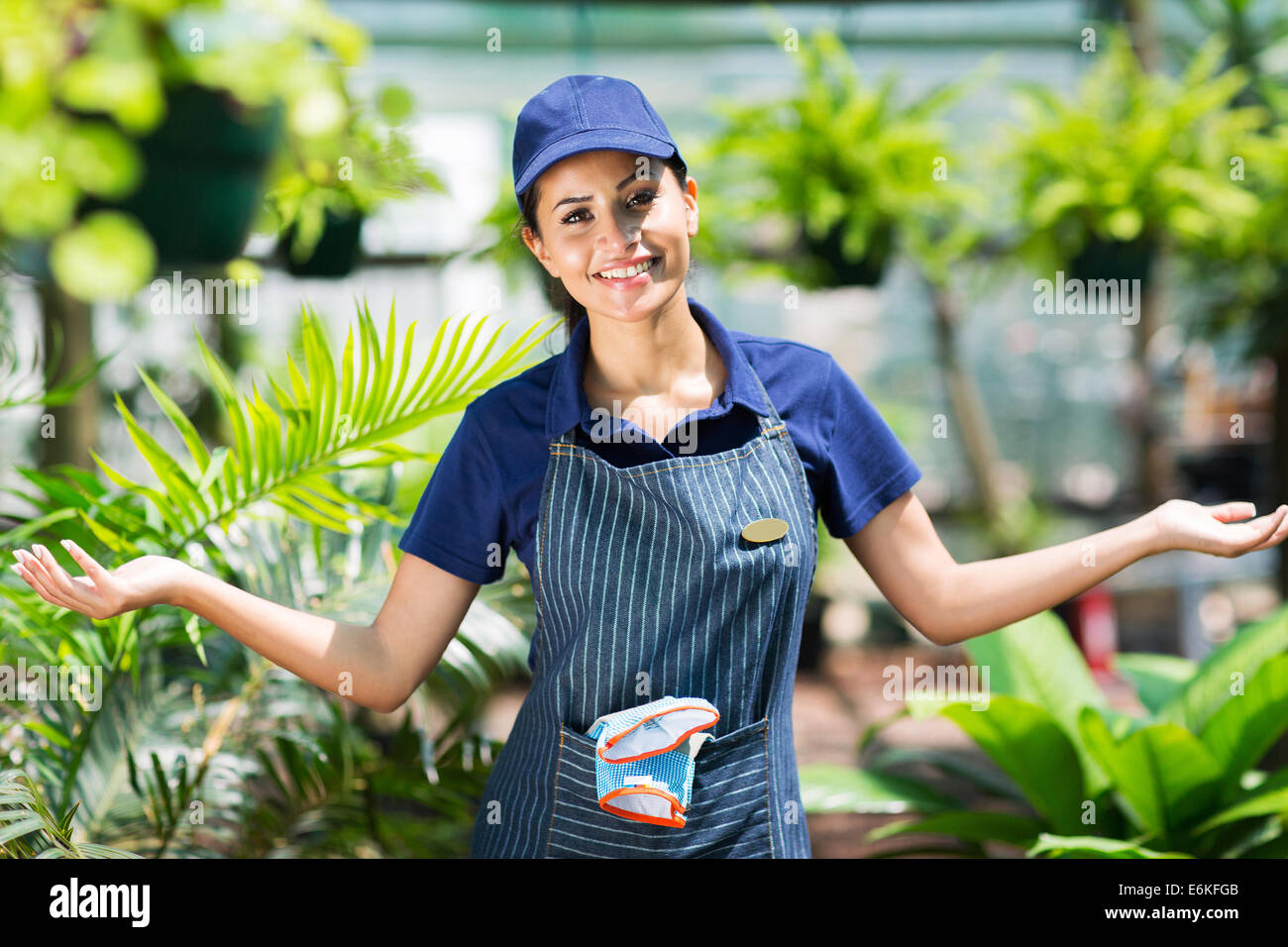 pretty female gardener with arms open in greenhouse - Stock Image