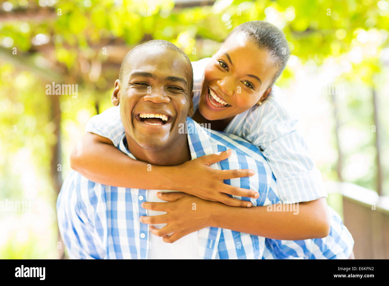 happy African woman enjoying piggyback ride on boyfriend outdoors - Stock Image