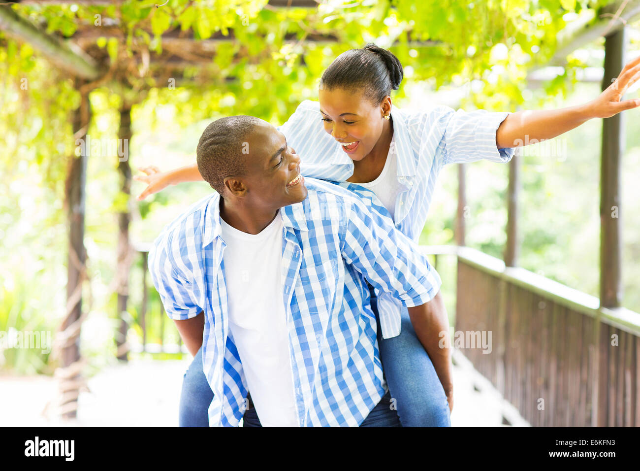 cheerful African American couple piggyback outdoors - Stock Image