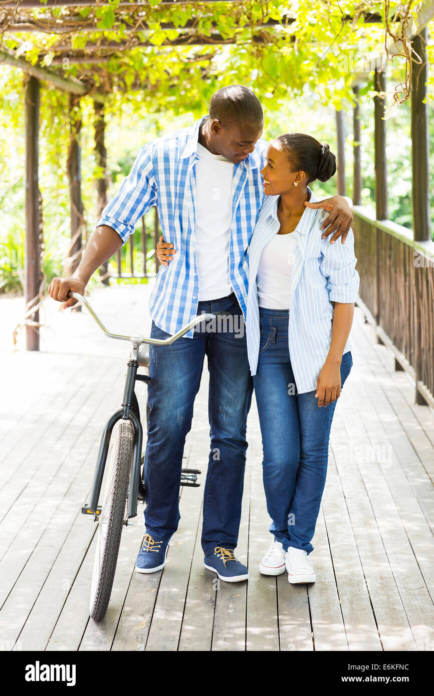 lovely African couple walking with a bike outdoors - Stock Image