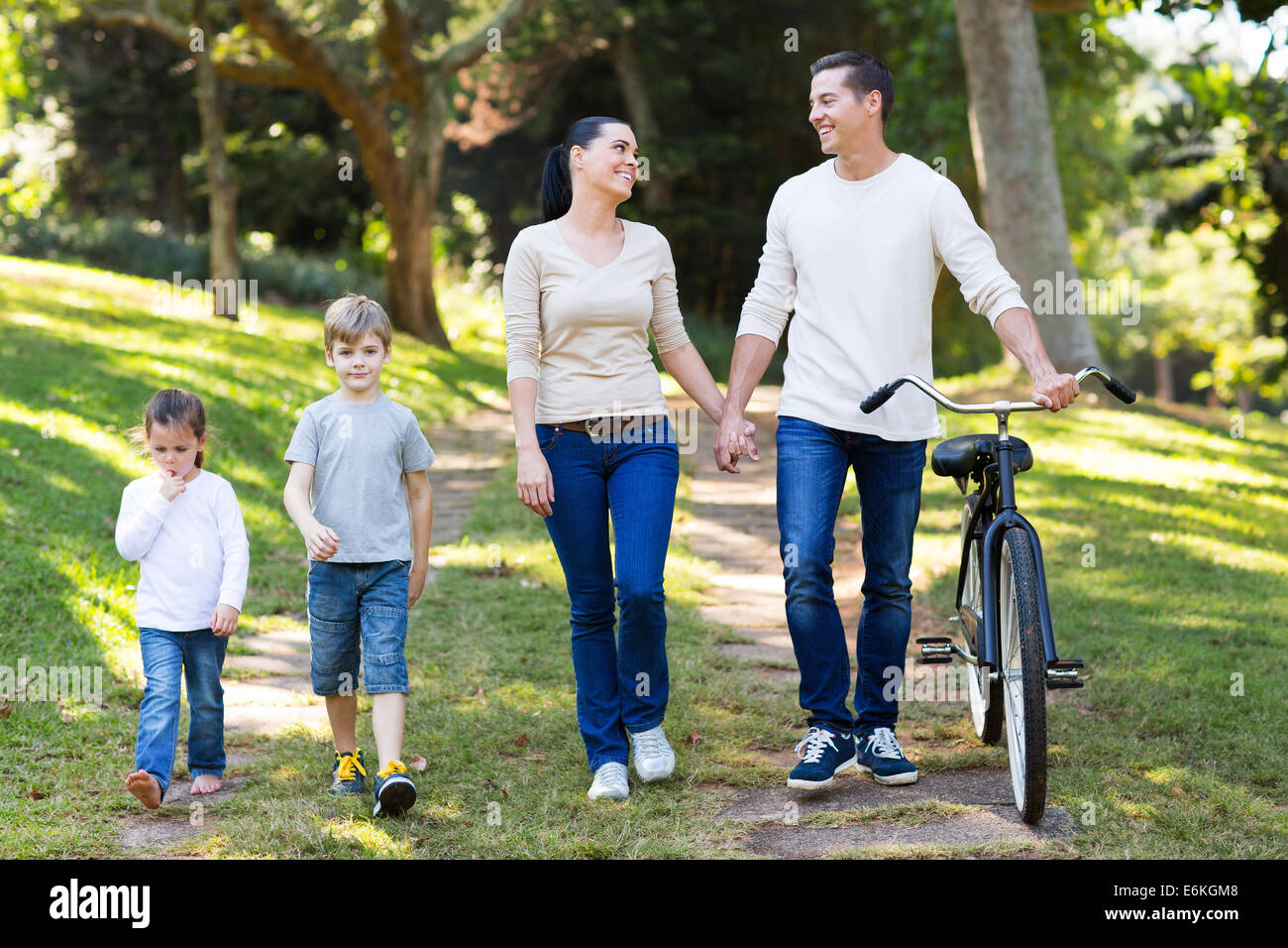 lovely young couple and kids walking outdoors in the park - Stock Image