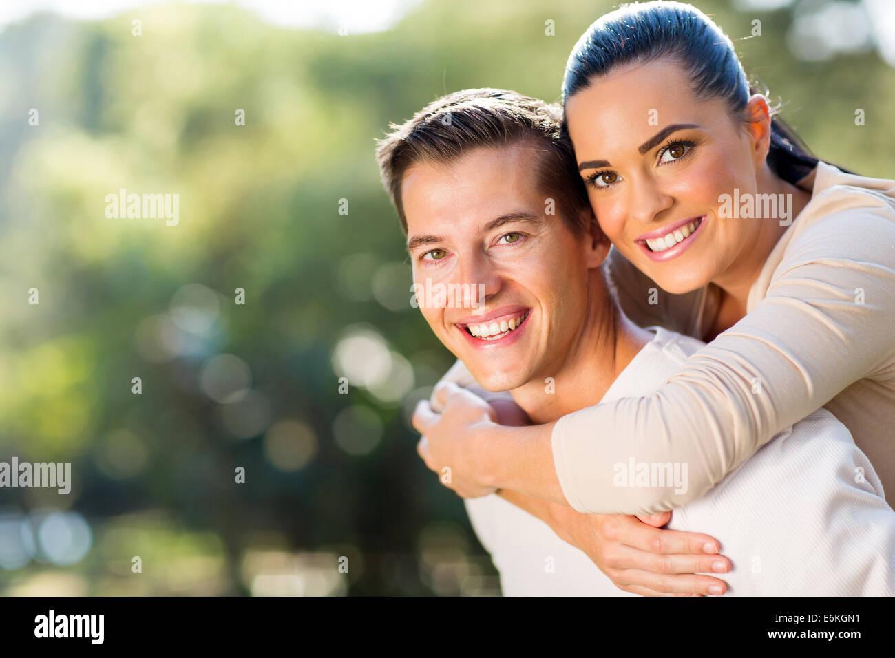 happy woman enjoying piggyback ride on boyfriends back outdoors - Stock Image