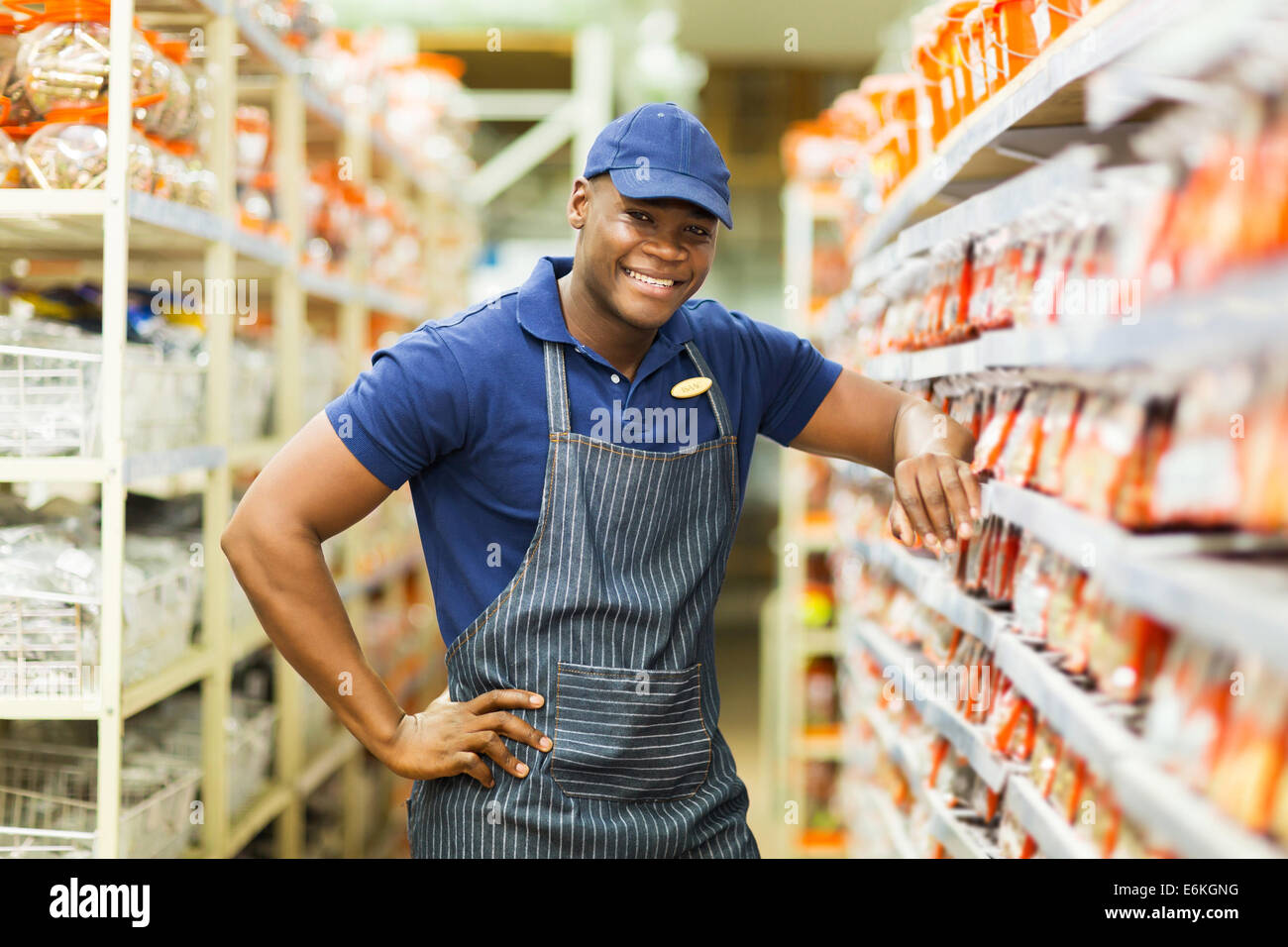 smiling African hardware store worker standing by the fasteners aisle - Stock Image