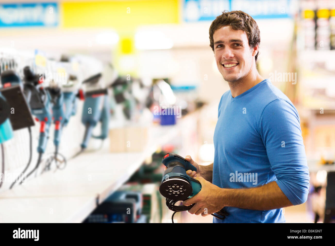 smiling young man purchasing a hand tool in hardware shop - Stock Image