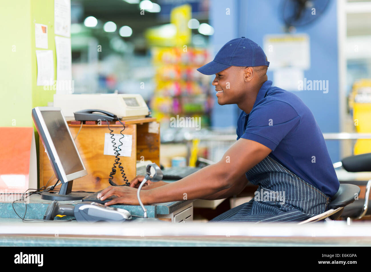 happy African male cashier working at till point in supermarket - Stock Image
