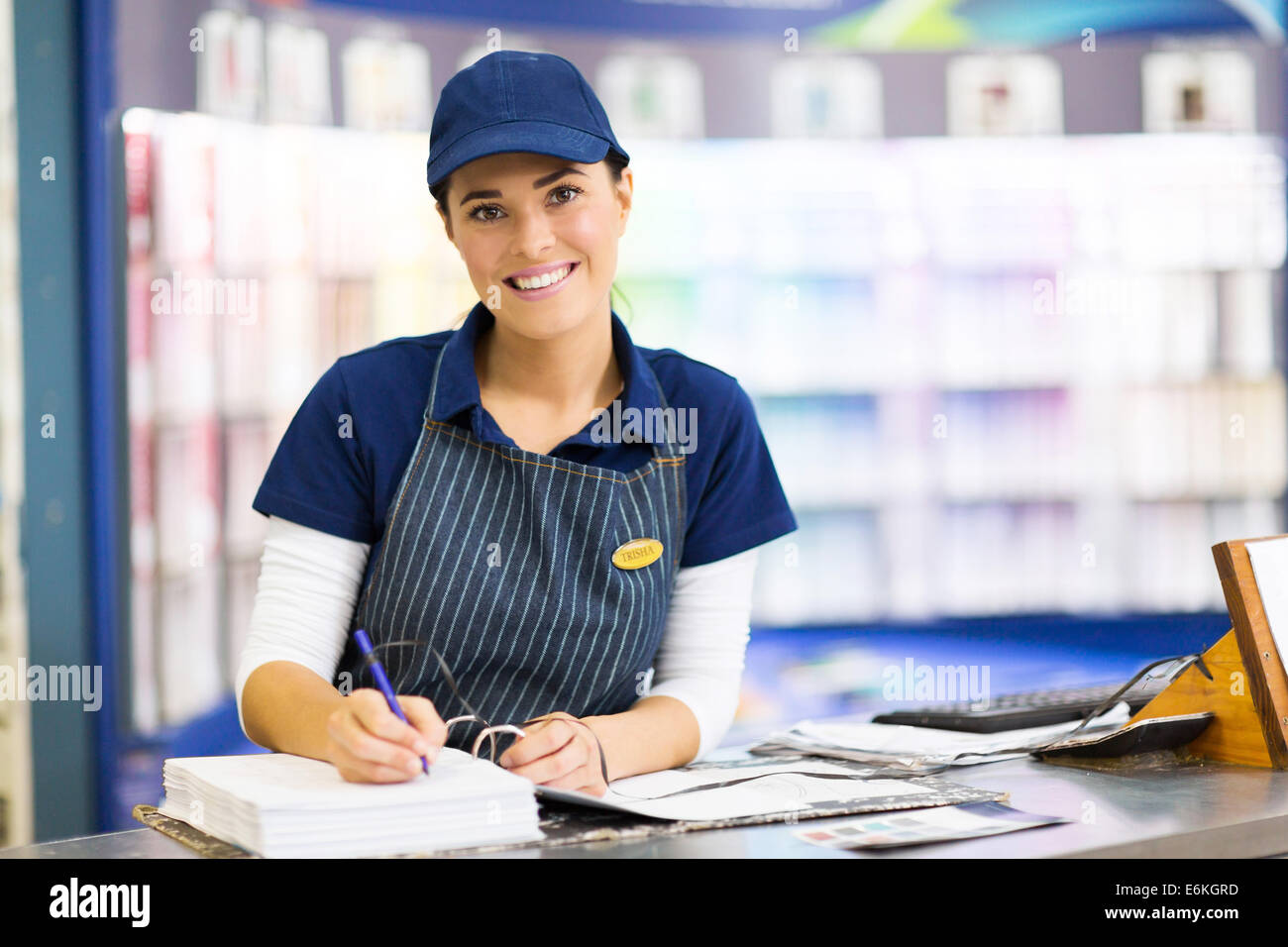 beautiful female paint store clerk working - Stock Image