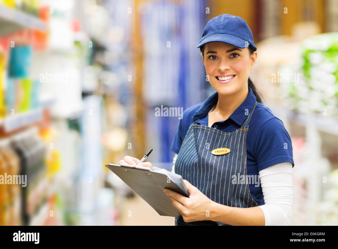 happy female clerk working in supermarket - Stock Image