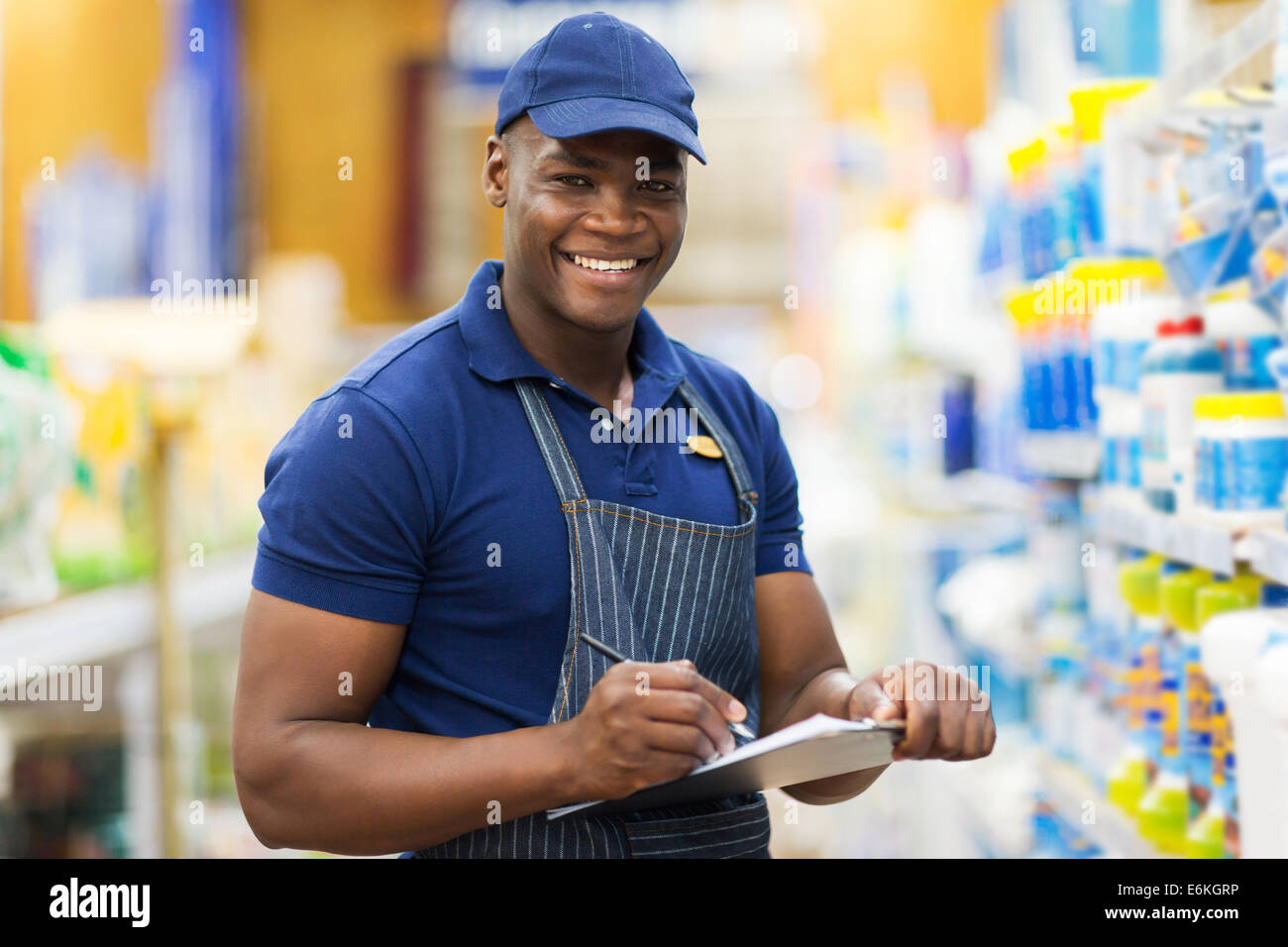 happy African shop assistant checking stock in supermarket - Stock Image