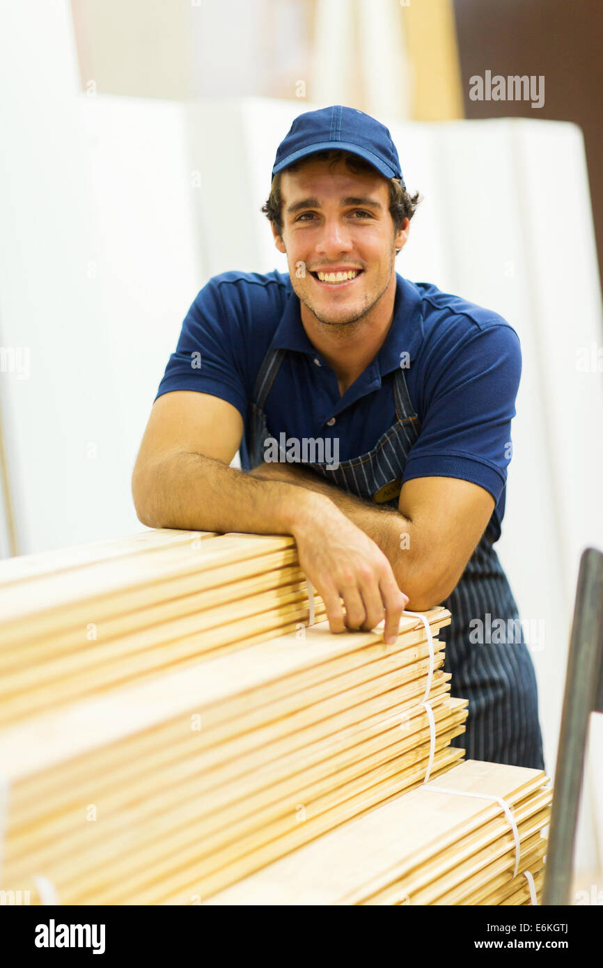 happy hardware store worker standing next to stacked wood - Stock Image