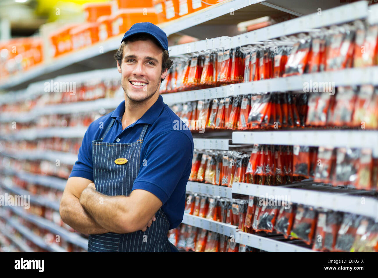 handsome hardware store salesman standing next to fasteners shelf Stock Photo