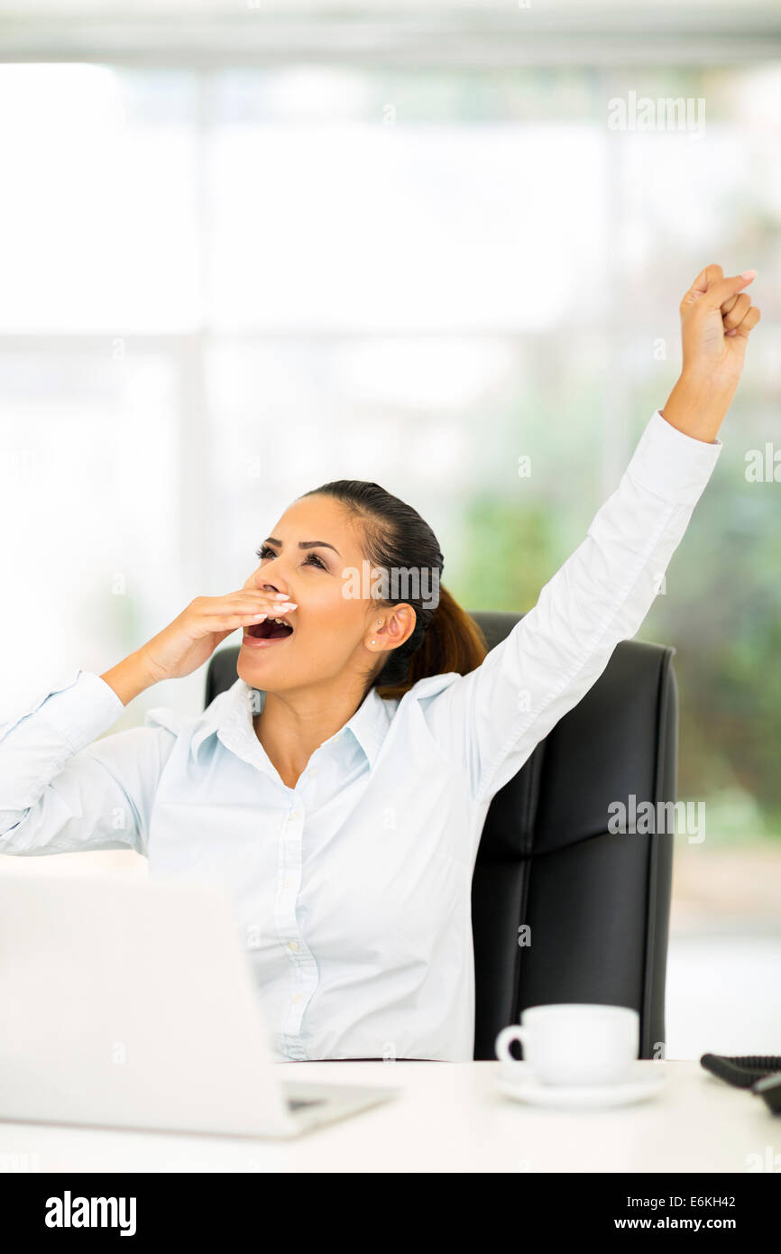 exhausted businesswoman yawning in office - Stock Image