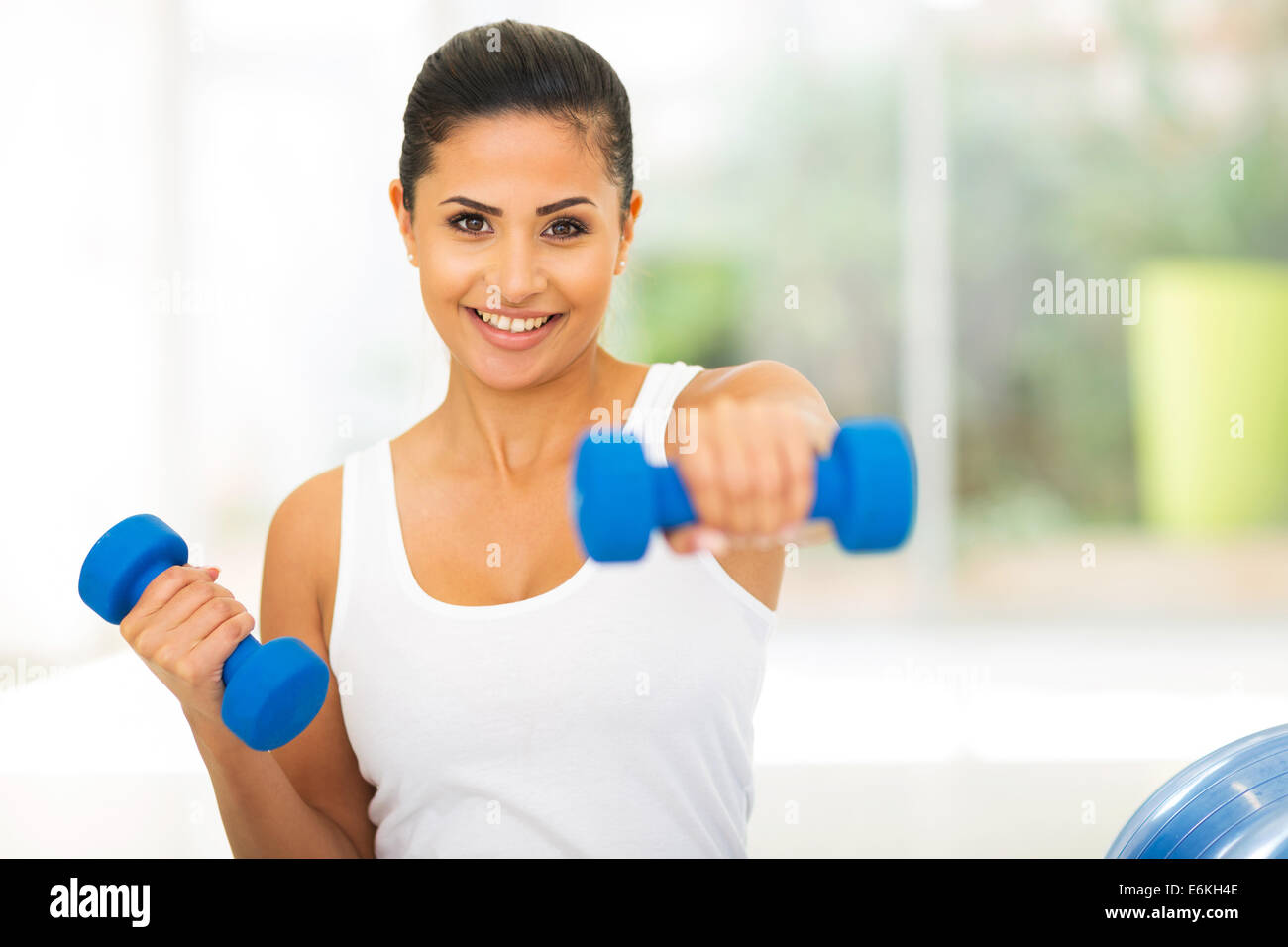 portrait of pretty woman working out with dumbbells - Stock Image
