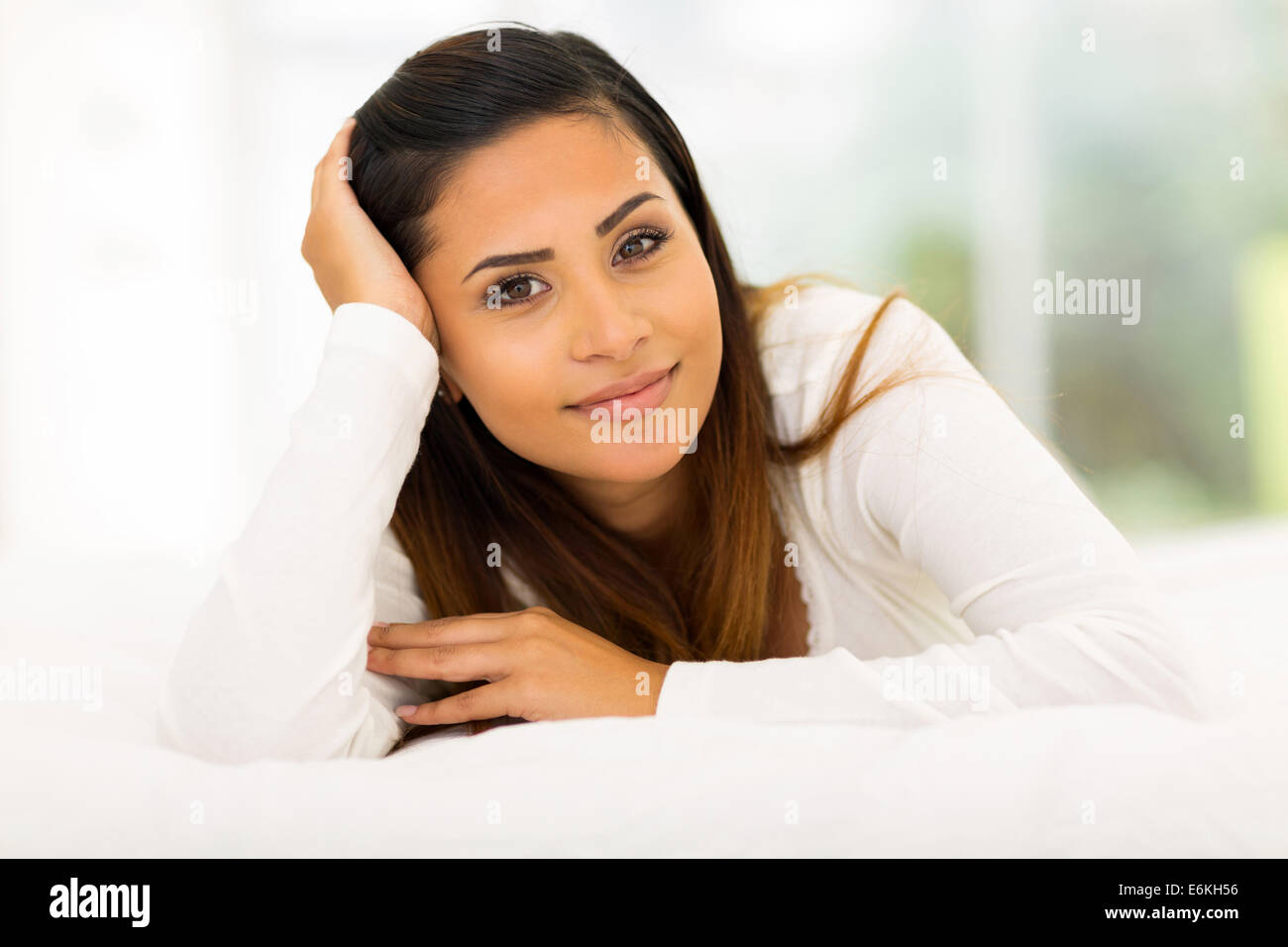 peaceful Caucasian girl lying in comfy bed at home - Stock Image