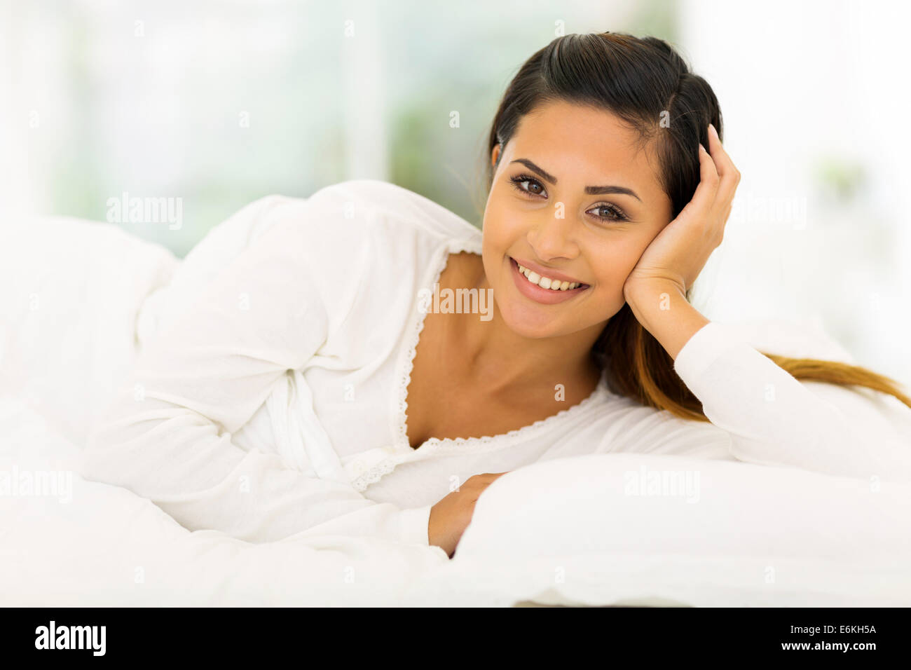 beautiful young woman lying in comfy bed - Stock Image