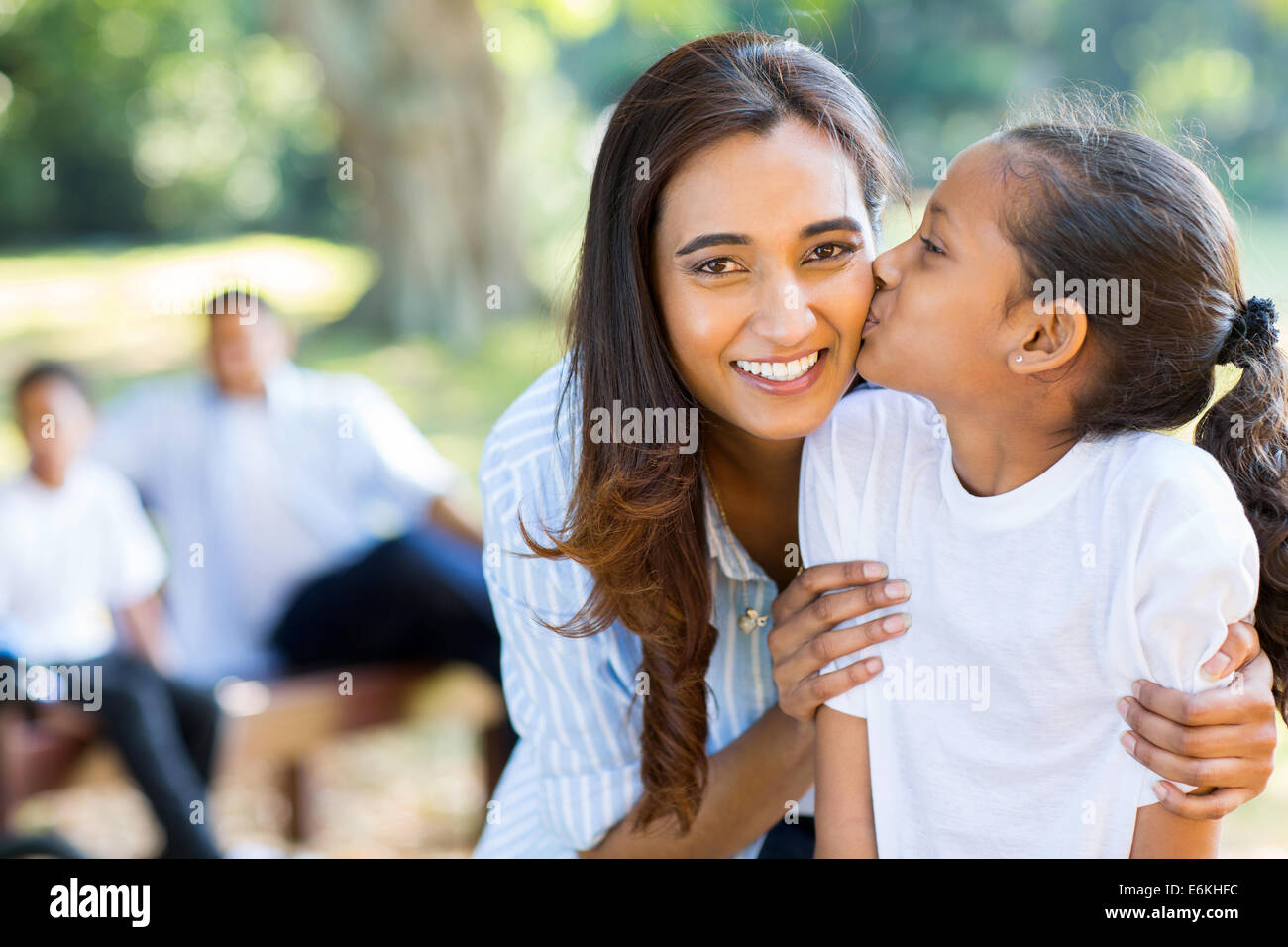 cute little Indian girl kissing her mother outdoors Stock Photo