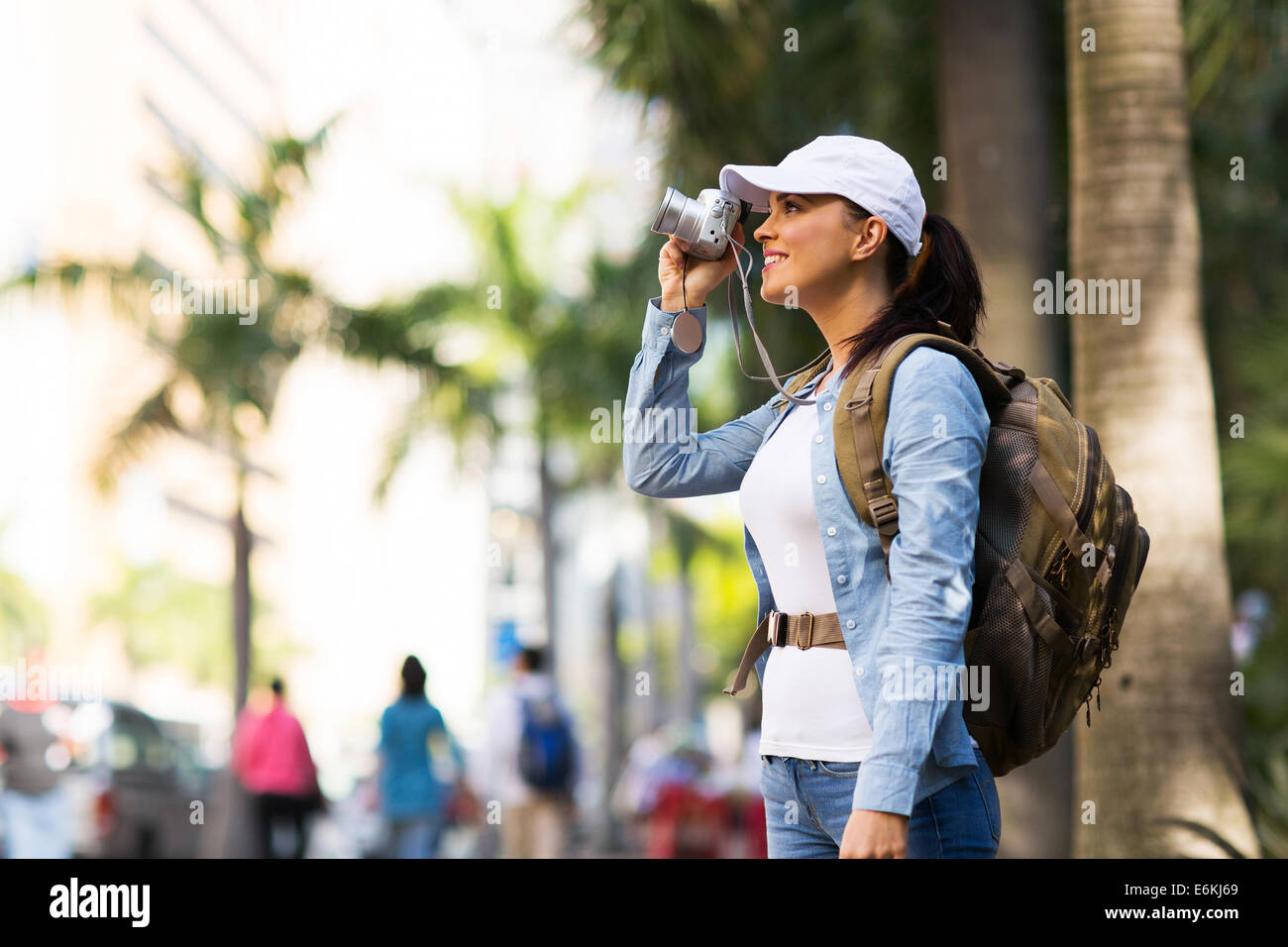 pretty female traveller taking photos in the city - Stock Image
