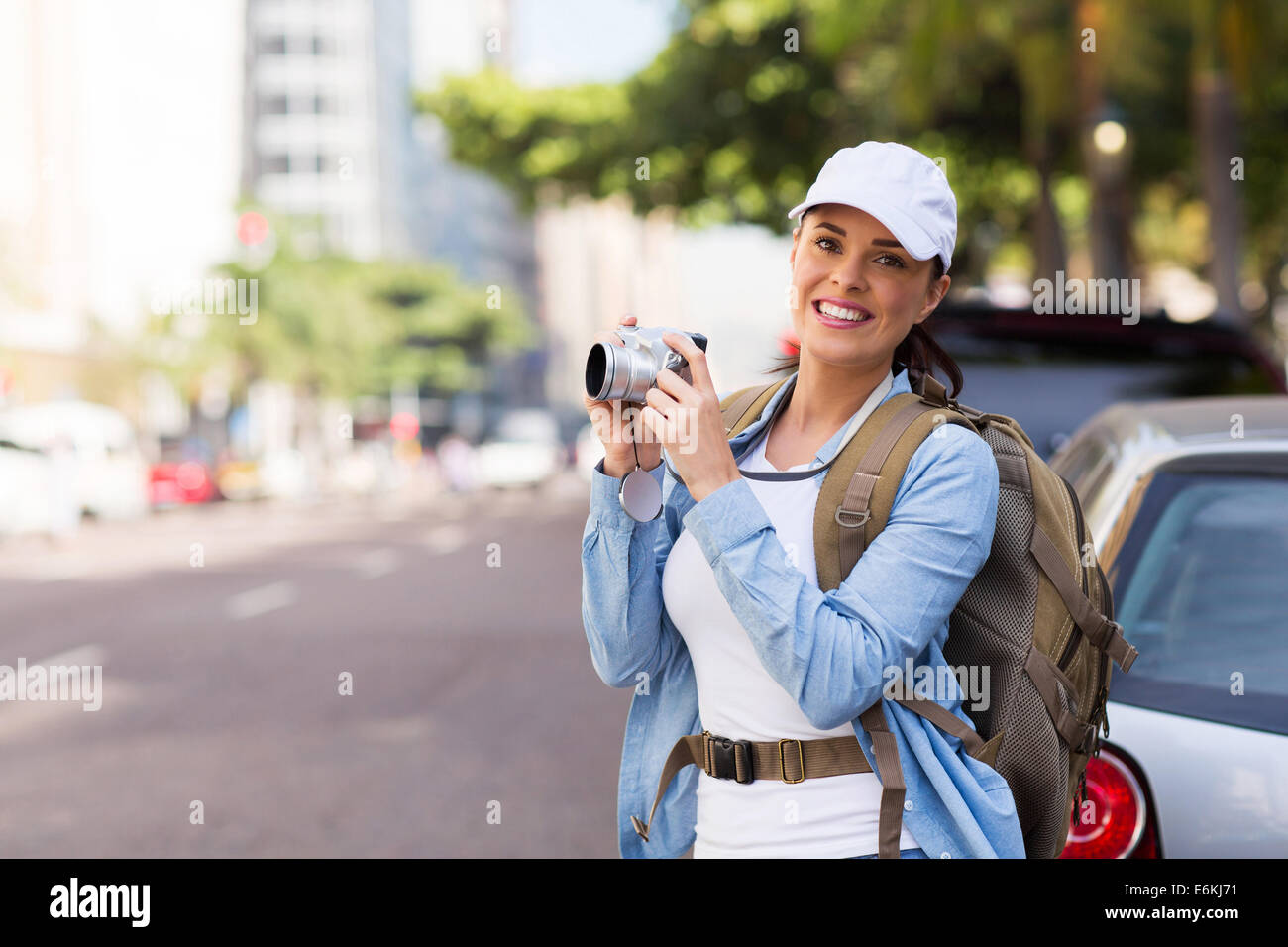 pretty tourist taking pictures with digital camera on urban street Stock Photo
